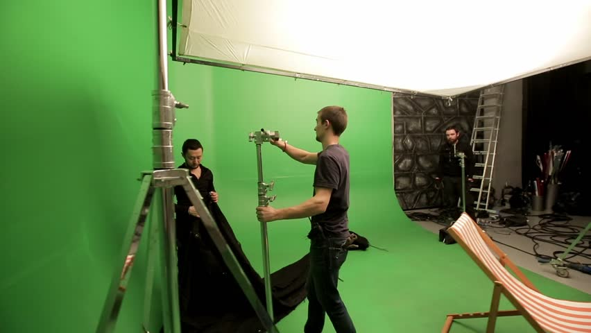 Moscow, Russia - December 4, 2016 : Film crew in green studio preparing, setting lighting professional equipment. Chroma is technology of combining two or more images or frames in single composition.