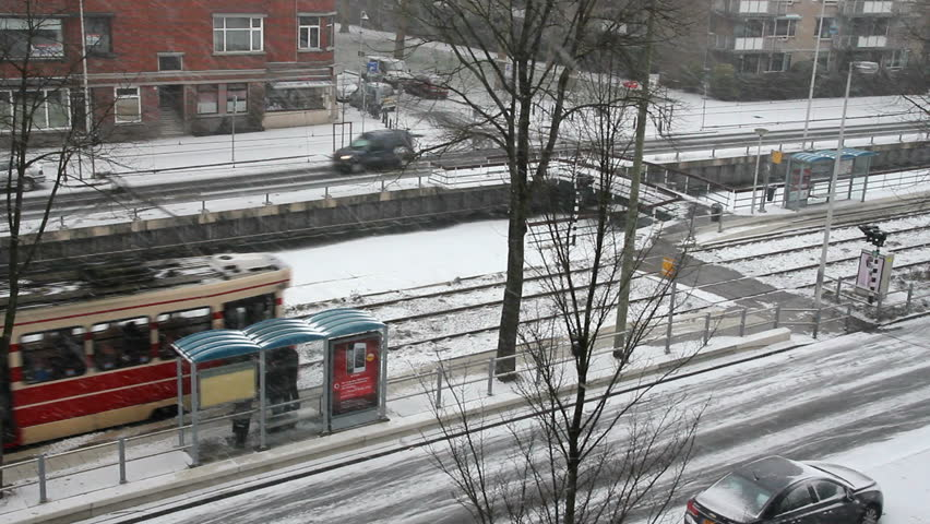 Tram drives away from a tram stop with snow everywhere