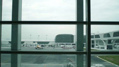 A view of planes through a window in an airport dolly shot