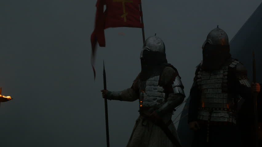 Sentinel. Knights. Evening. Medieval guard. Strong wind. Fog. Smoke. Medieval camp. The flag with the Orthodox cross. Torches. Reconstruction of the X century. 10th century.