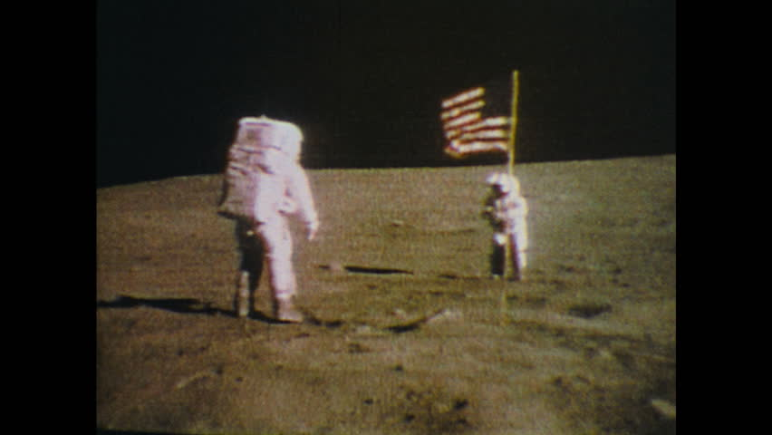 UNITED STATES: 1970s: Men on moon salute USA flag. Astronauts walk on moon