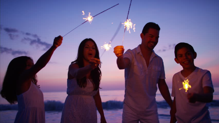 Silhouette Hispanic family travel resort relax sparklers party fun Summer holiday beach sunset dusk RED DRAGON