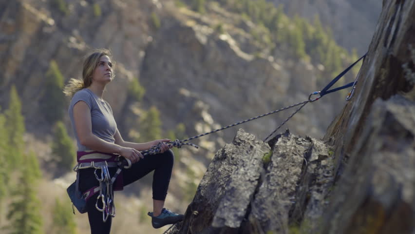 Young Woman Rock Climbs To Top Of Route, Looks Around At View, Then Smiles At Her Partner Below