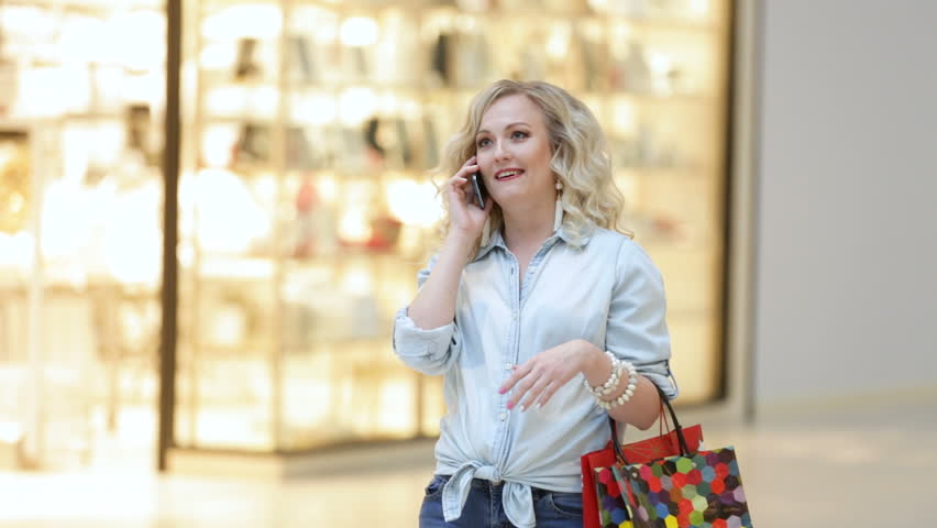 Beautiful girl in the mall is calling on the phone | Shutterstock HD Video #22108810