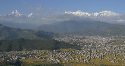 Panoramic view of big city surrounded by mountains. City in Himalayas. Many houses and rice fields near snow covered mountains.