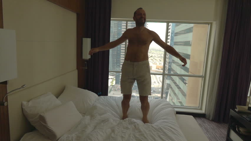 Young, happy man having fun, jumping on bed in room, super slow motion 240fps  | Shutterstock HD Video #22129459