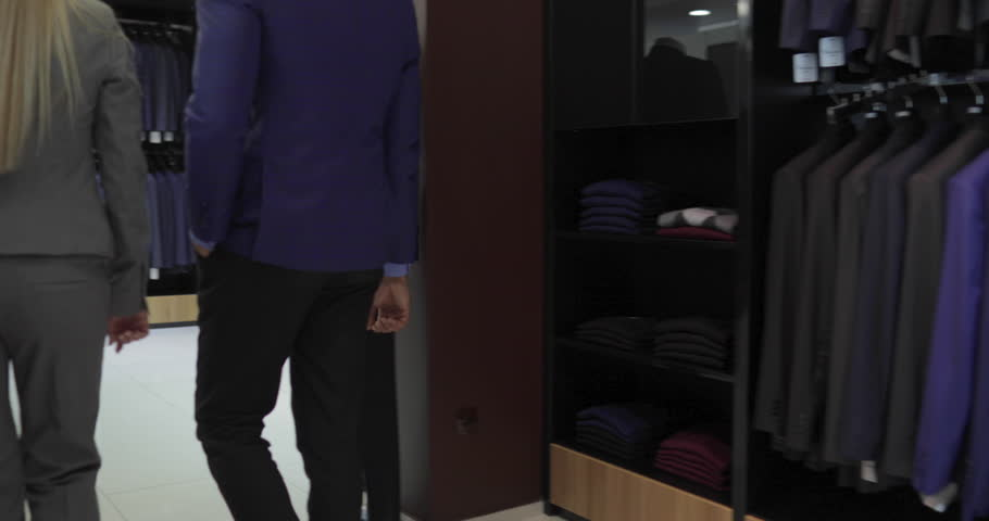 Business Man Enter Fashion Shop, Customer Choosing Suit Clothes In Retail Store, Shopping Seller Woman Show Formal Wear Slow Motion 60 Fps   Shutterstock HD Video #22130149