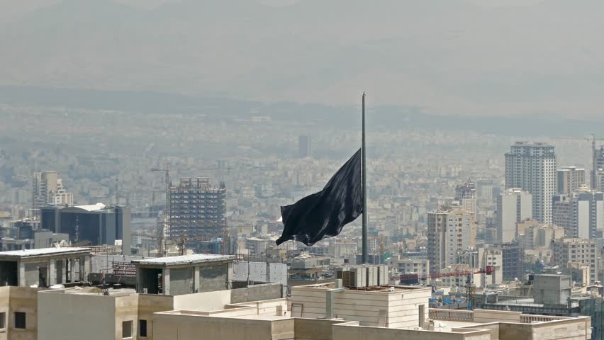 Black flag the symbol of Islam waving in wind over buildings of a big city