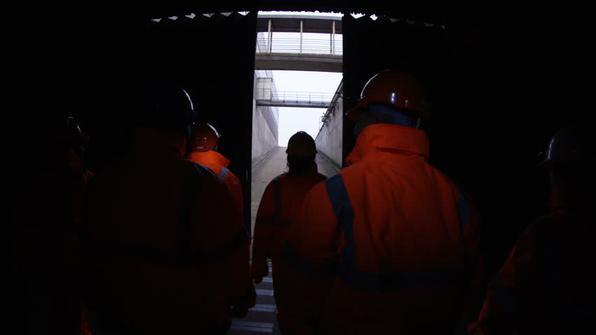 4K Workers at a fuel plant walking into the light