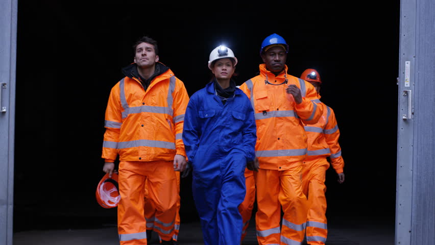 4K Team of workers at fuel plant come up from underground & walk into daylight