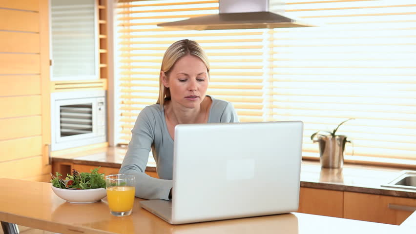 Woman drinks a glass of orange juice while looking at a laptop screen | Shutterstock HD Video #2219179
