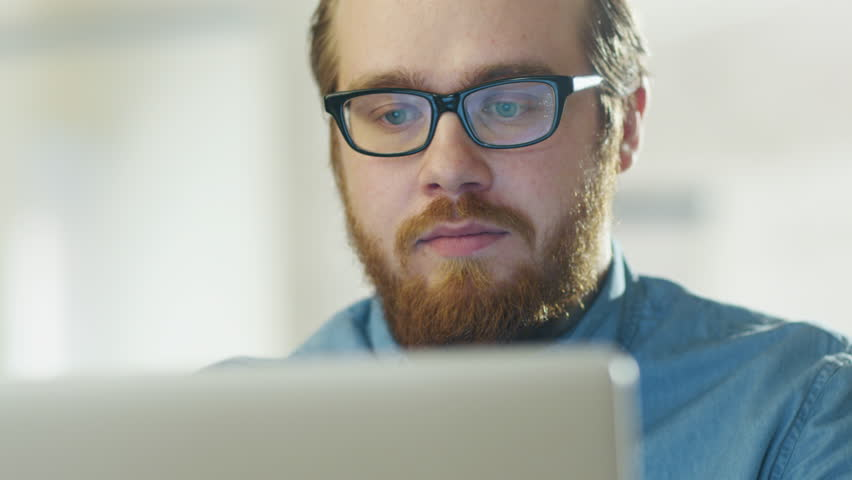 Portrait of a Bearded Young Man Wearing Glasses Sitting in His Office Working on a Computer. Computer Screen Reflects in His Glasses. Shot on RED Cinema Camera in 4K (UHD). | Shutterstock HD Video #22195267