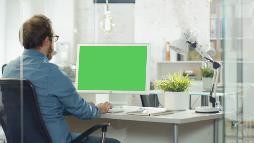 Young Man with a Beard Actively Works on His Desktop Computer. He Sits In His Modern Studio/Office. He's Computer Screen is Green Mock-up. Shot on RED Cinema Camera in 4K (UHD). | Shutterstock HD Video #22195348