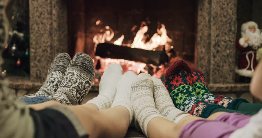Cinemagraph - Feet in woolen socks warming by cozy fire in Christmas time in slow motion. Loop. Family with two kids warming their feet by the fireplace in winter time. 120 fps 4k motion photo.