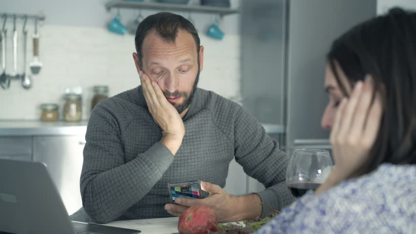 Sad, unhappy couple counting bills on smartphone and laptop in kitchen at home