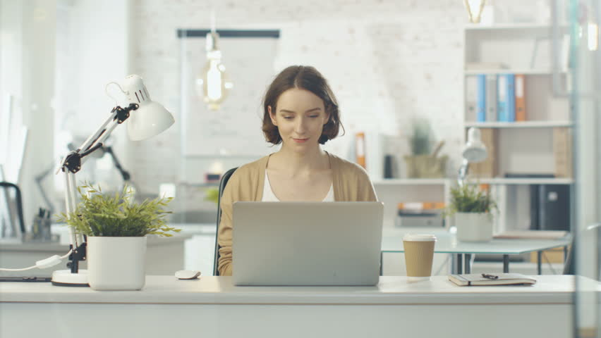 Portrait Shot of a Creative Woman Sitting at Her Desk. Using Notebook. She Sits in a Light and Modern Office. Shot on RED Cinema Camera in 4K (UHD).