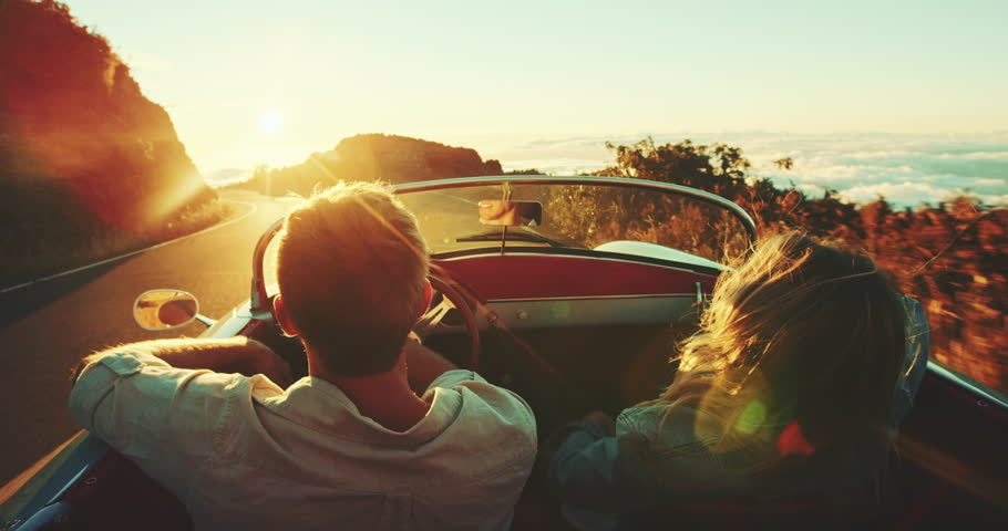 Happy couple driving on country road into the sunset in classic vintage sports car #22242868