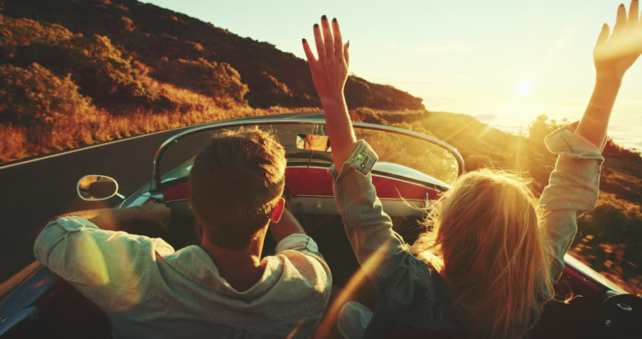 Happy couple driving on country road into the sunset in classic vintage sports car #22242874