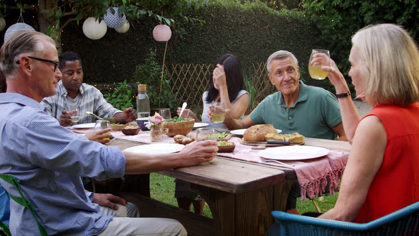 Mature Friends Enjoying Outdoor Meal In Backyard Shot On R3D | Shutterstock HD Video #22267852
