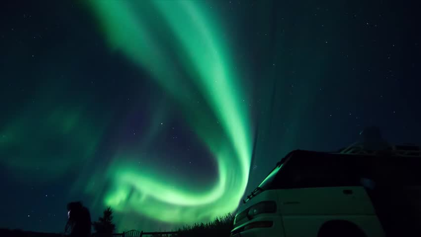Timelapse video of Icelandic northern lights in autum time with peoples watching it and sitting on the car.