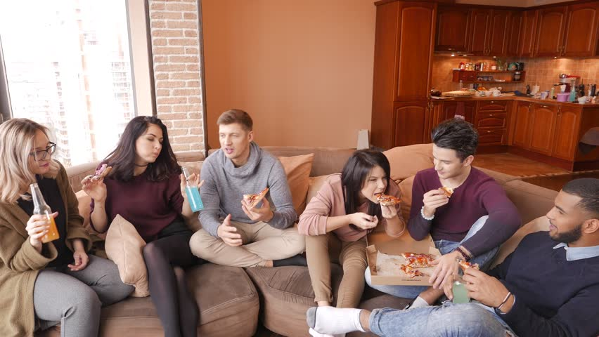 Group of multi ethnic young friends eating pizza in home interior #22299295