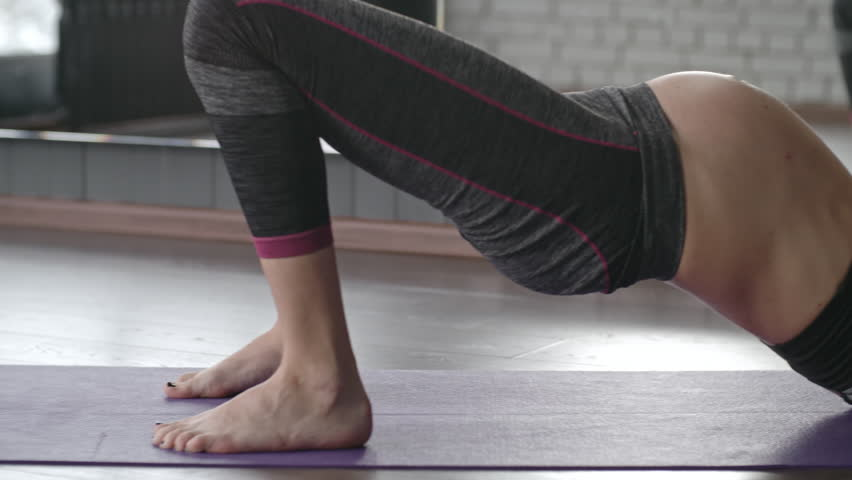 Tilt down of pregnant woman doing bridge pose on mat with raised straight arms | Shutterstock HD Video #22323124