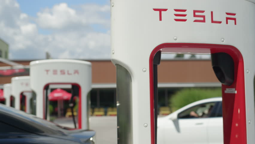 LJUBLJANA, SLOVENIA - JULY 10 2016: Black Tesla autonomous electric cars refilling energy at Supercharger charging station. White luxury vehicle coming and parking to fill battery at sunny day