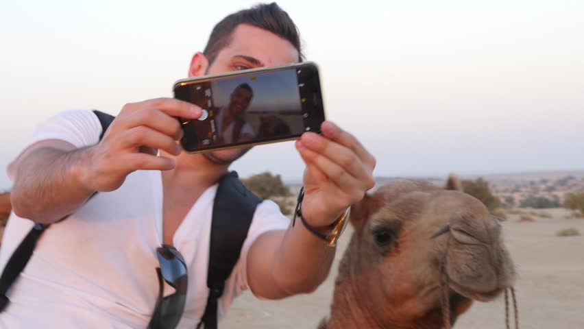 Man taking a selfie with a Camel in Desert