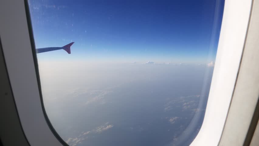 Looking out of the plane through window, small clouds blue sky, plane wing. Camera moving to the window and looking out from the plane to sky panorama above clouds at cruising altitude #22367728