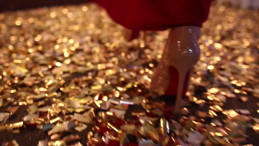 A woman in a long red dress and patent-leather shoes walks a glitter floor. Gold bokeh effect.