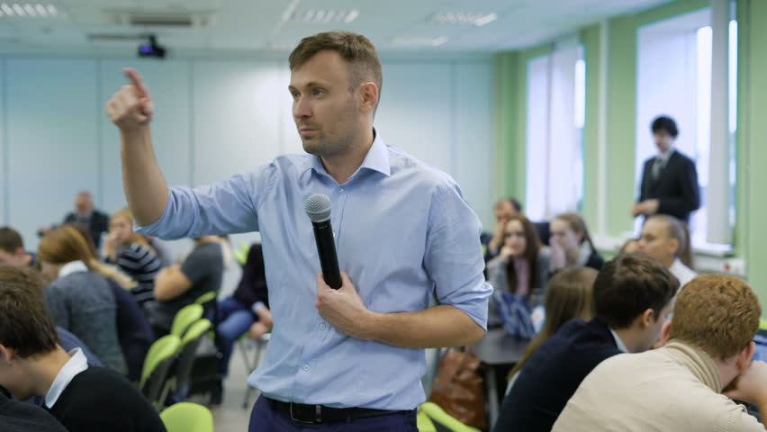 Professional coach in blue shirt speaking into the microphone and gesticulating at workshop for future top managers of a business company. Audience sitting at the conference room at the table Royalty-Free Stock Footage #22394929