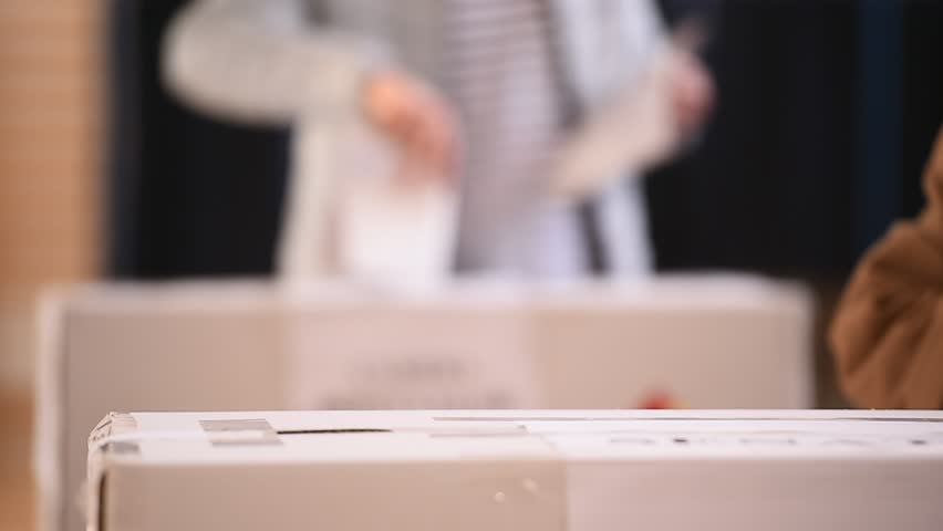 Unrecognizable people casting votes into the ballot box during elections