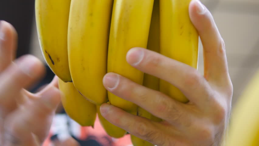 Male hand selecting bananas at the supermarket. Man taking a bunch of bananas from counter in a grocery store. Guy selecting fresh fruit at produce department of shop. Buyer chooses food. Close up