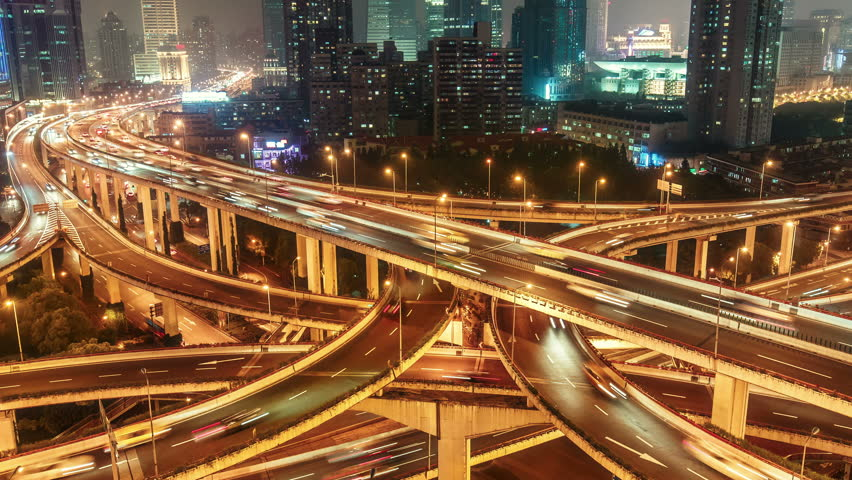Complex highways in Shanghai, China, at night. Scenic aerial view of big illuminated interchange with fast moving cars. 4K Time lapse.