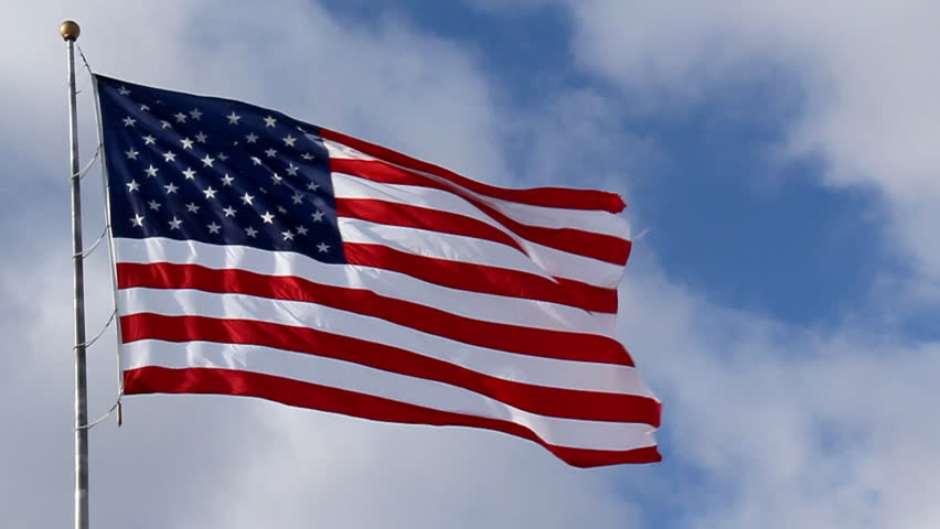 American Flag Waving against Blue Sky. American flag waving against blue sky and white clouds. Filmed at 60 fps and slowed down to 30 fps.