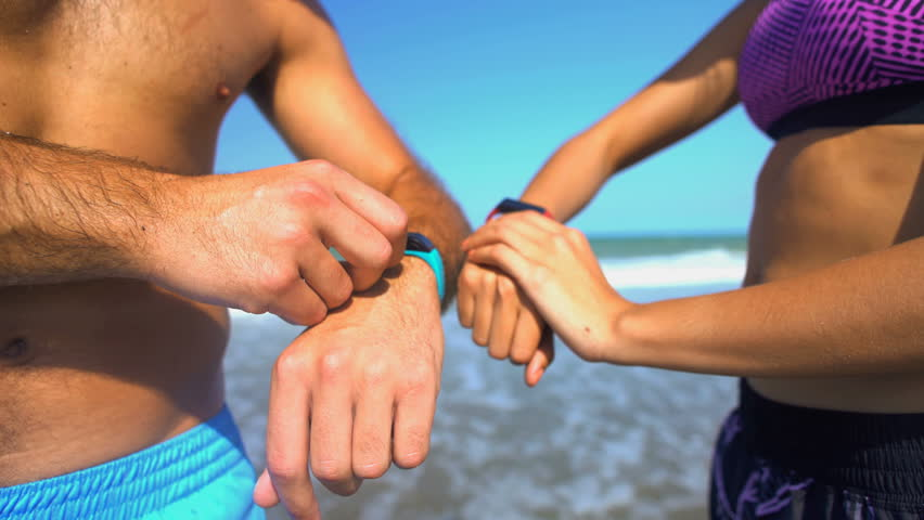 Multi ethnic male and female using sport watch technology to keep fit and healthy on their beach holiday #22457548