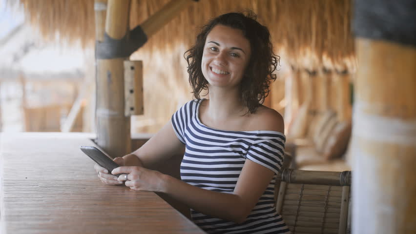 Tanned young girl sitting at the outdoor bar under a straw umbrella holding a tablet computer in the hands and fervently laughs | Shutterstock HD Video #22467853