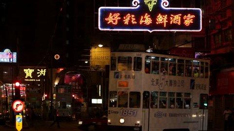 CIRCA 2010: WS Trolley driving on street at night / Hong Kong, China