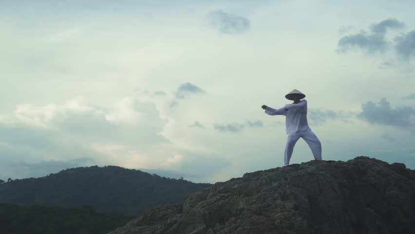 Man in white uniform training martial arts forms alone for defense training and its health benefits | Shutterstock HD Video #22481488