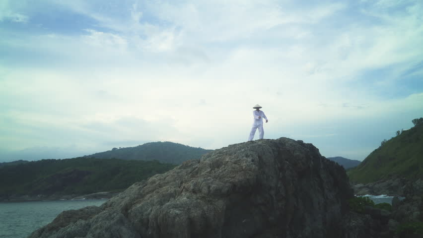 Young man practicing performs tai chi moves on the rocks in front of the ocean | Shutterstock HD Video #22481509