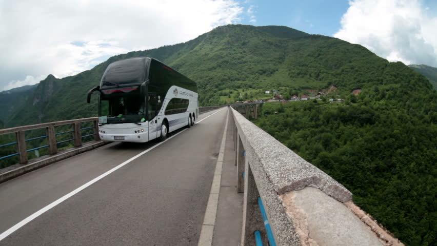 MONTENEGRO - CIRCA JUN, 2016: Passenger tourist bus drives on Durdevica bridge. Traffic is on rural road across Tara river. The Durdevica bridge is attraction in Durmitor national park