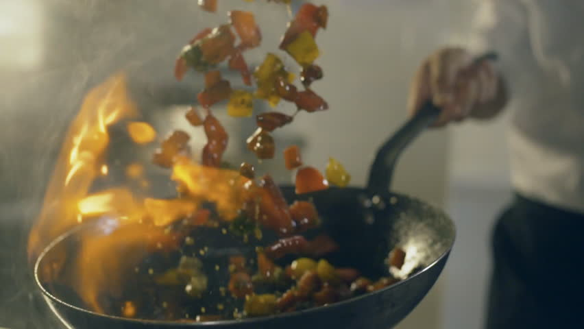 Chef in restaurant kitchen doing flambe on vegetables, close up   Shutterstock HD Video #22487185