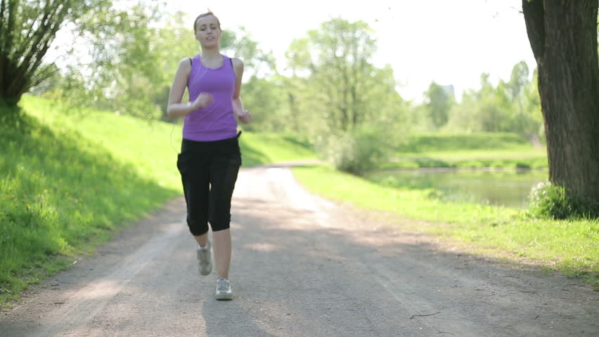 Young blond woman taking breath after jogging