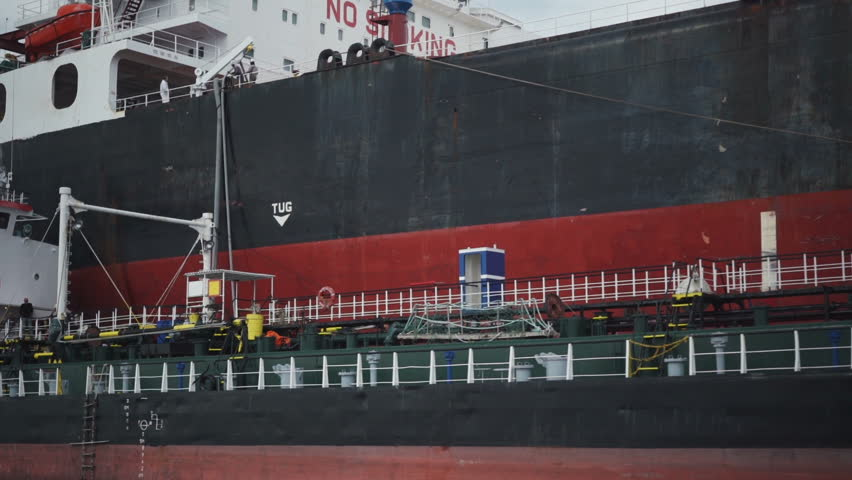 Anchored cargo ship refueled with diesel by a fuel barge, close up