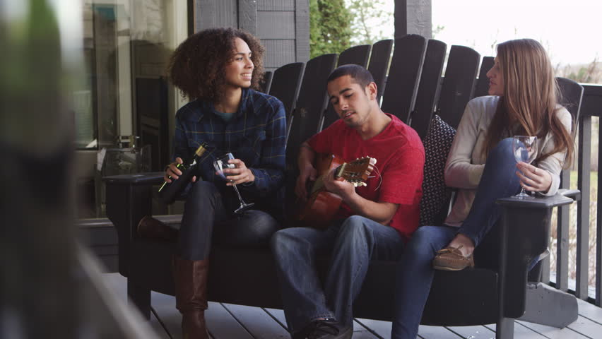 Three friends hanging out on pation drinking wine while playing guitar | Shutterstock HD Video #22507309