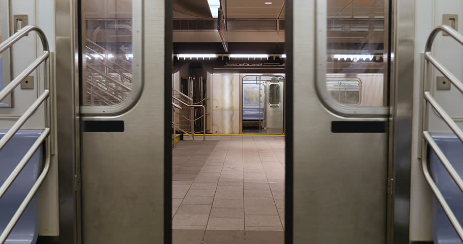 An interior view of the doors on a New York City subway car as they open at an empty platform.  No passengers, perhaps during a pandemic like COVID-19 or Coronavirus.