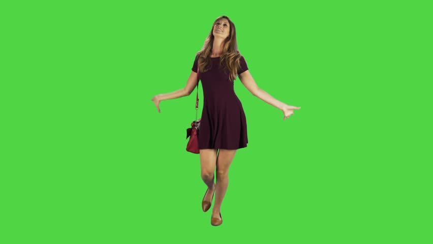 Young woman walking towards camera, goofing around in a full body shot over a green screen.