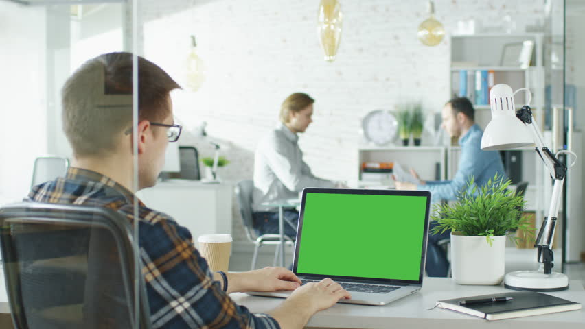 Close-up of a Man Sitting at His Desk with Green Screen Laptop. In Background Blurred and Brightly Lit Office where Two Young Man Shake Hands and Sit Down For Conversation. Shot on RED EPIC (uhd). | Shutterstock HD Video #22521070