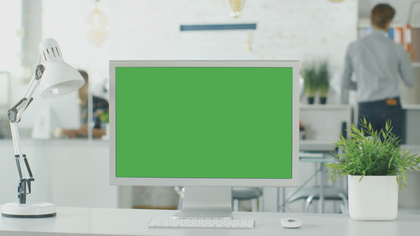 Close-up of a Green Screen on a Personal Computer. In Background Blurred and Brightly Lit Office where People go Through Office Routine. Shot on RED EPIC (uhd). | Shutterstock HD Video #22522120