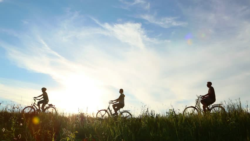 Family of three people having ride together in rural landscape. Son, mother and father riding bikes over sunset blue sky background. Family bikers having fun on vacations. Real time full hd video.